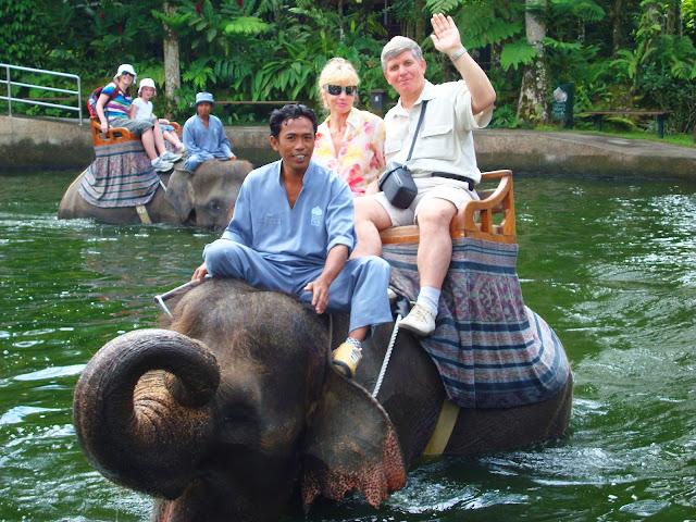Изображение троих людей на слоне в воде, остров Бали, Индонезия