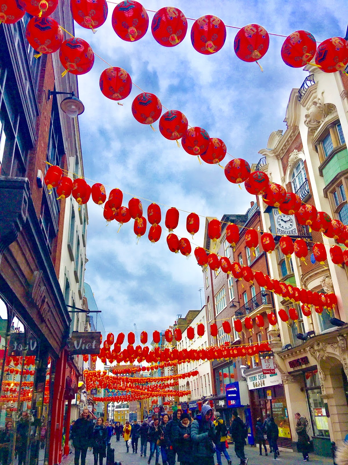 Photo of a street, the angle of the camera is pointing upwards. Chinese New Year laterns can be seen, with blue skiers in the background. The street is full of people.