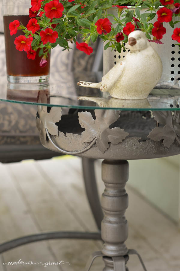 Create an outdoor accent table using a metal plant stand and piece of glass. |  www.andersonandgrant.com
