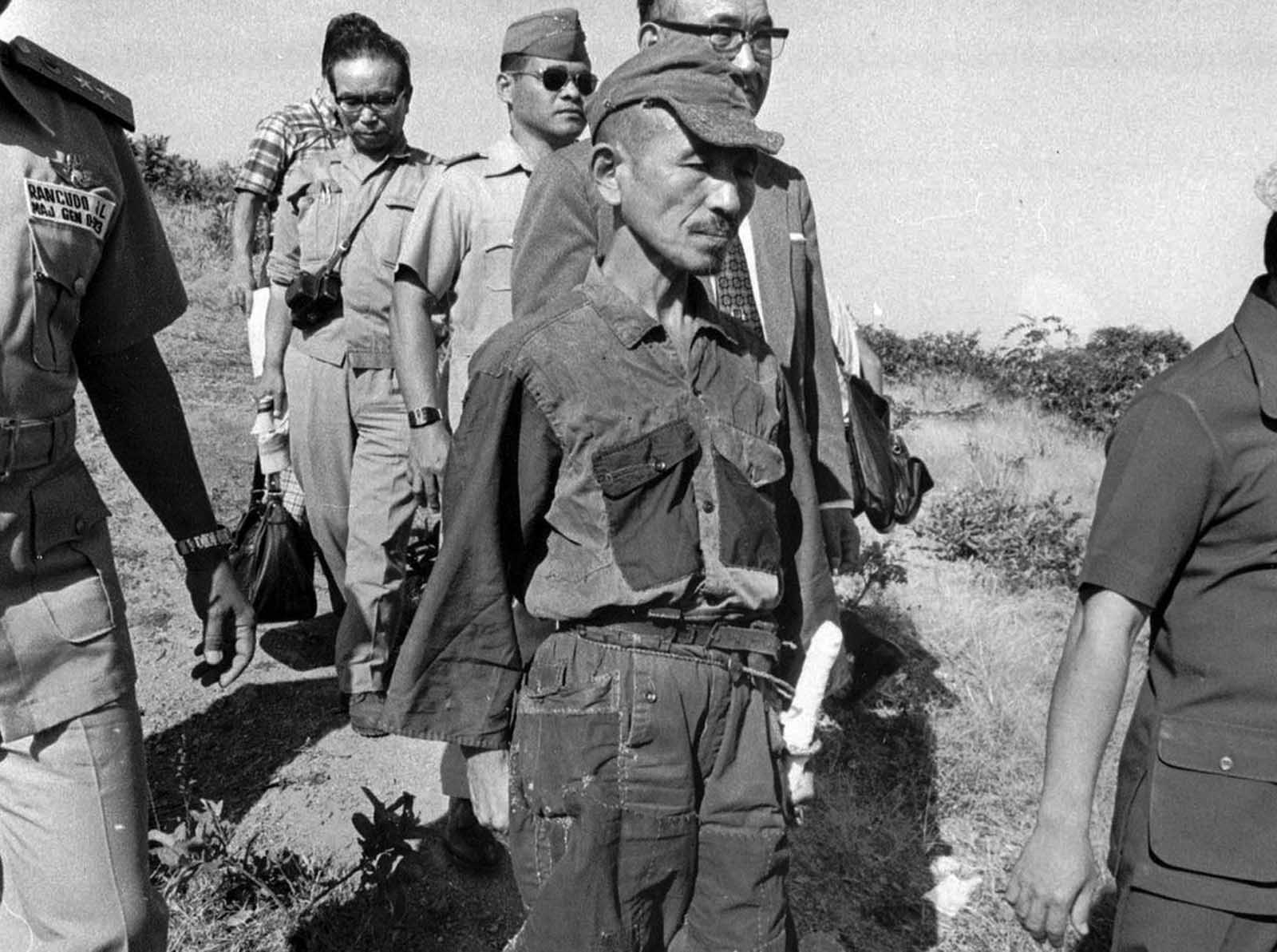 In March of 1974, some 29 years after the official end of World War II, Hiroo Onoda, a former Japanese Army intelligence officer, walks out of the jungle of Lubang Island in the Philippines, where he was finally relieved of duty. He handed over his sword (hanging from his hip in photo), his rifle, ammunition and several hand grenades. Onoda had been sent to Lubang Island in December of 1944 to join an existing group of soldiers and hamper any enemy attacks. Allied forces overtook the island just a few months later, capturing or killing all but Onoda and three other Japanese soldiers. The four ran into the hills and began a decades-long insurgency extending well past the end of the war. Several times they found or were handed leaflets notifying them that the war had ended, but they refused to believe it. In 1950, one of the soldiers turned himself in to Philippine authorities. By 1972, Onoda's two other compatriots were dead, killed during guerrilla activities, leaving Onoda alone. In 1974, Onoda met a Japanese college dropout, Norio Suzuki, who was traveling the world, and through their friendship, Onoda's former commanding officer was located and flew to Lubang Island to formally relieve Onoda of duty, and bring him home to Japan. Over the years, the small group had killed some 30 Filipinos in various attacks, but Onoda ended up going free, after he received a pardon from President Ferdinand Marcos.