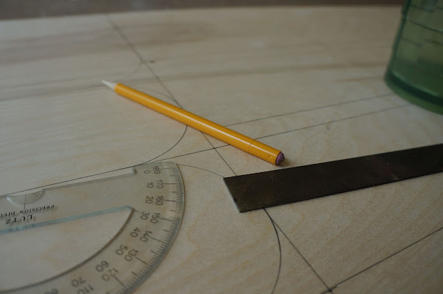 pencil marks on sheet of plywood marking components of flatpack stools