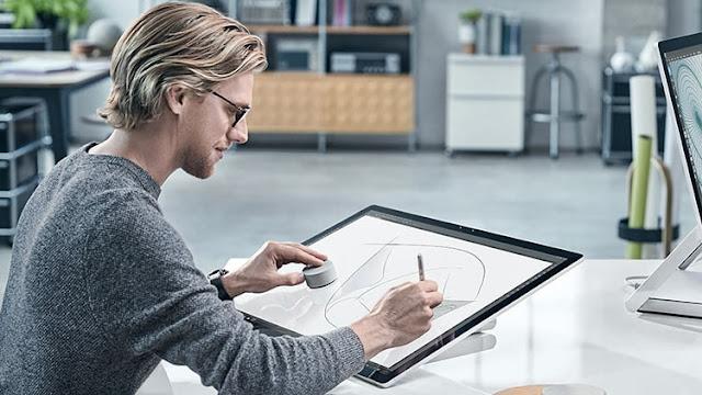 дизайнер работает за моноблоком Microsoft Surface Studio