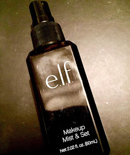 A large rectangular black bottle with elf in bold big white font with liquid inside on a bright background.
