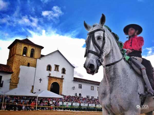 Jinete en su caballo e iglesia principal de Villa de Leyva con público asistente al fondo