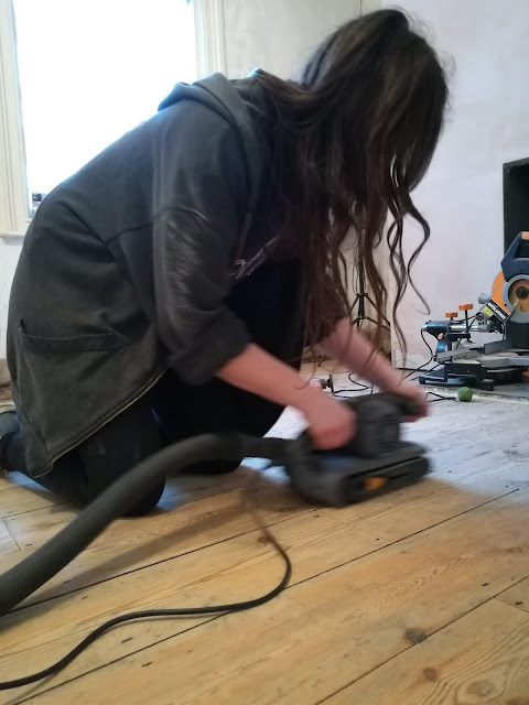 Using a belt sander on floorboards
