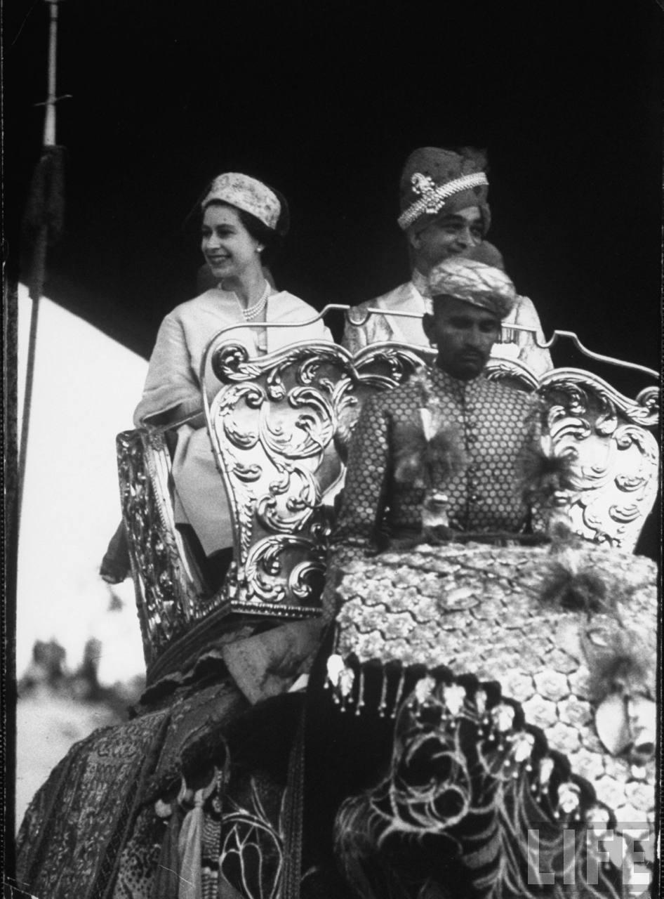 Queen Elizabeth II riding on elephant, sitting beside maharaja in howdah.