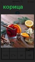 На столе стоит стакан, на верху которого лежит корица с долькой лимона и огарок свечи стоит