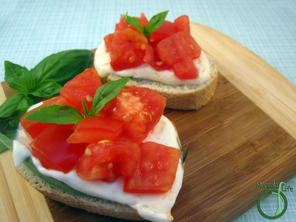 Morsels of Life - Caprese Crostini - Toasted bread topped with mozzarella cheese, a basil leaf, and tomatoes for a Caprese crostini. Fancy it up with a balsamic reduction if you'd like.