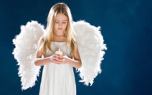 Meisje verkleed als engel met een kaars in haar handen