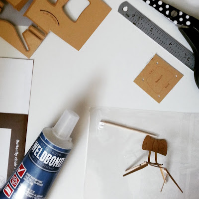 Glue, ruler, scissors and toothpick plus a half-built cardboard model of a 1958 Ercol butterfly chair.