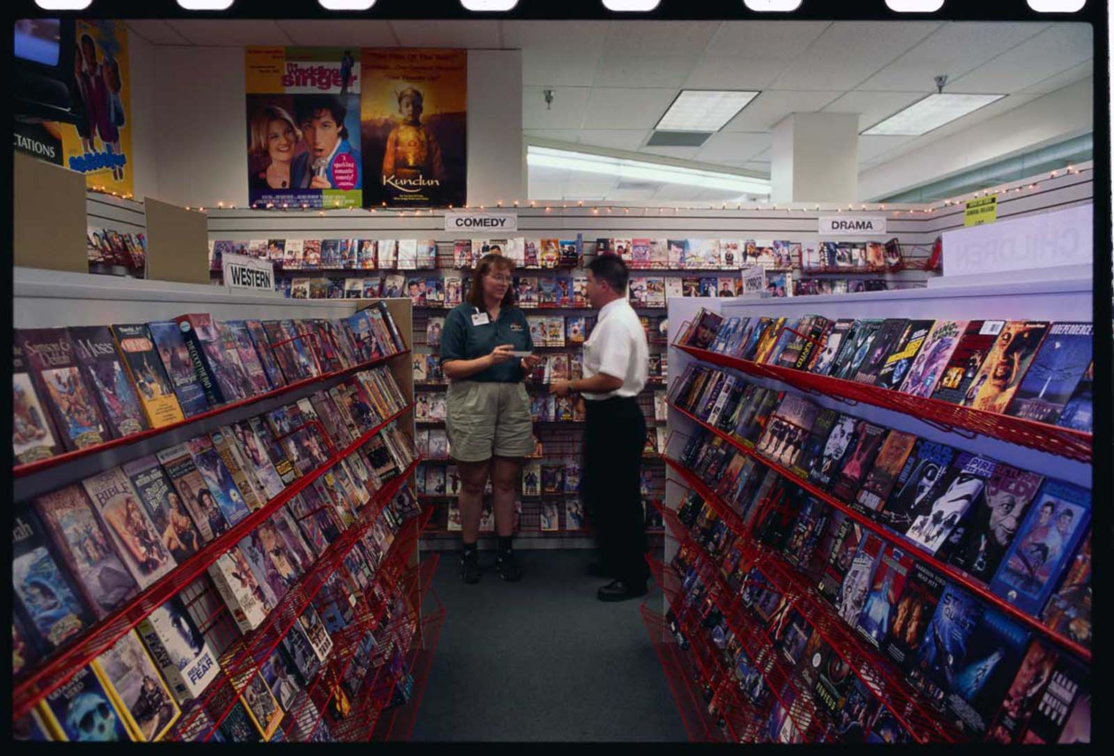 Store manager Ken Broderius talks with an employee in the video rental department of the Rosaurs Super One.