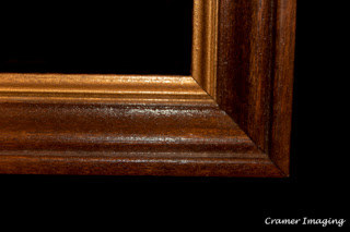 Cramer Imaging's photograph of a single brown wooden picture frame corner on a black background