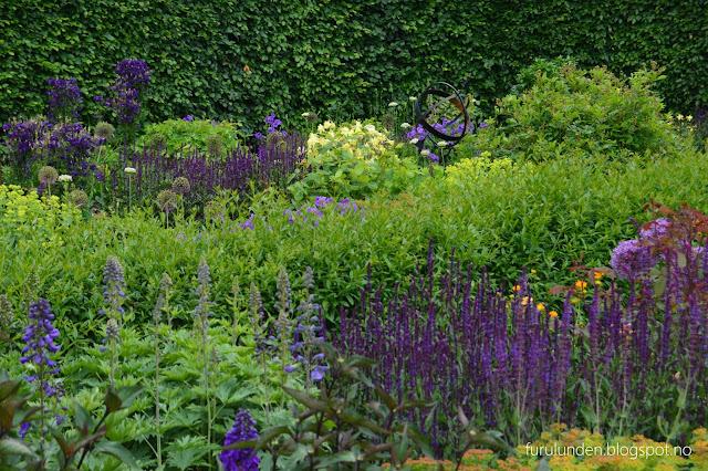 Historikk og oppskrift på en cottage garden. Solur midt i et overdådig blomsterbed