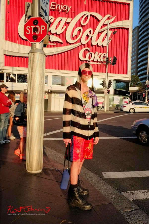 The famous Coke sign in Kings Cross and a strangly fitting person standing in front of it in matching red items. Photography by Kent Johnson.