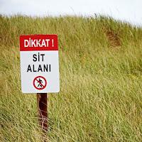 Otlu bir arazide üzerinde sit alanı uyarısı olan bir tabela