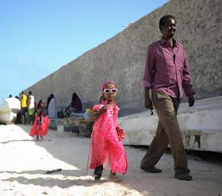 A little girl and her father walk on Lido beach in Mogadishu, Somalia, during Eid al-Fitr, the Muslim holiday marking the end of Ramadan.