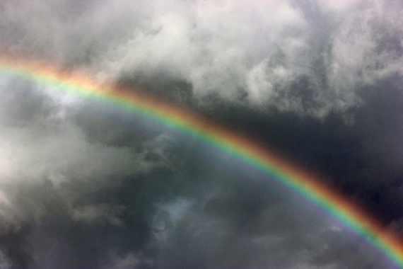 rainbow against dark gray storm clouds