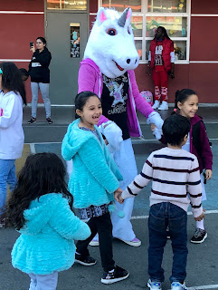 "students dance with Bessie Carmichael's mascot ""Bessie the Unicorn"""
