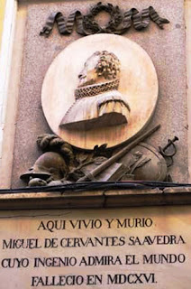 Sobre la placa conmemorativa se sitúa en alto relieve el perfil de la efigie de Cervantes tallado en un medallón y debajo los adornos.