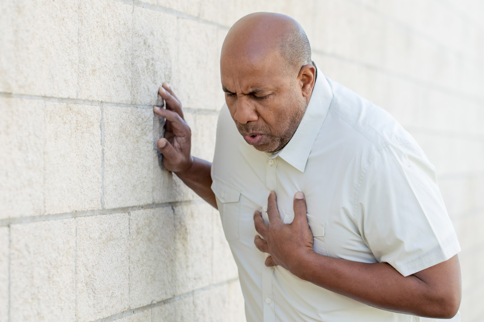 Man gripping his chest as if in pain