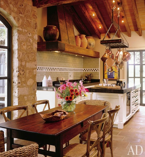 A natural farmhouse kitchen with tons of textures - brick and natural stone, a stunning tile backsplash and grand barn house wooden beams