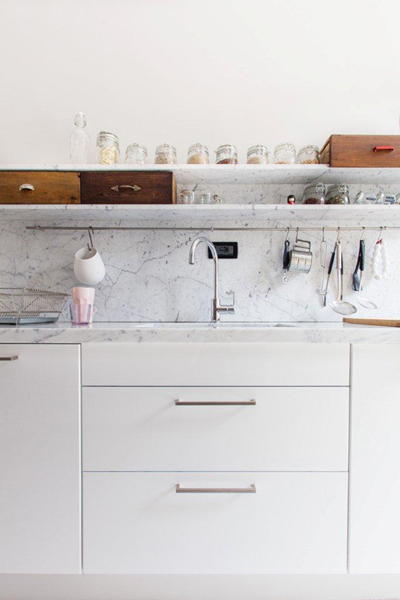 Kitchen with sleek white cabinetry and beautifully styled marble open shelving. Image via Cote Maison