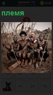 Индейцы из племени сидят на земле с копьями в боевой раскраске, готовые бежать на охоту