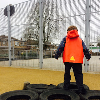 Child in a bright red raincoat plays in tyres in a school playground surrounded by fences