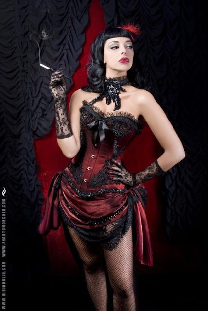 Women's steampunk burlesque or steampunk showgirl costumes and clothing. Red and black corset with skirt, fascinator, fishnet stockings and cigarette holder. For burlesque performers, pin-ups or boudoir photography