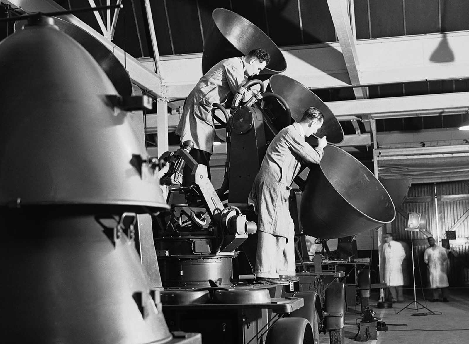 Workmen fit a set of paraboloids in a sound detector for use by anti-aircraft batteries guarding England, in a factory somewhere in England, on July 30, 1940.