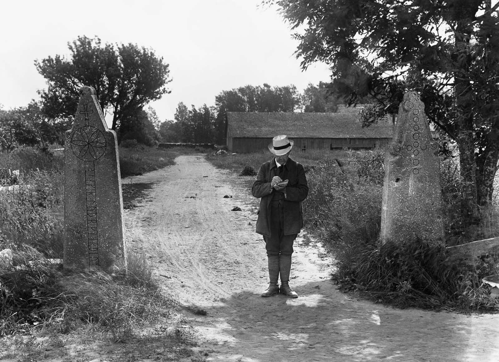 Linguist and runologist Otto von Friesen stands between medieval gateposts on the island of Gotland. The left gatepost reads,