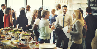 group of friends in business casual dress networking around a buffet table