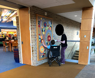 An older child in wheelchair, next to an adult female, is touching a colorful tile mosaic with floral motif hanging on a brick wall.