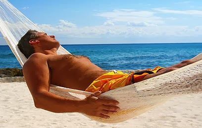 hombre acostado en chinchorro tomando sol a orillas del mar