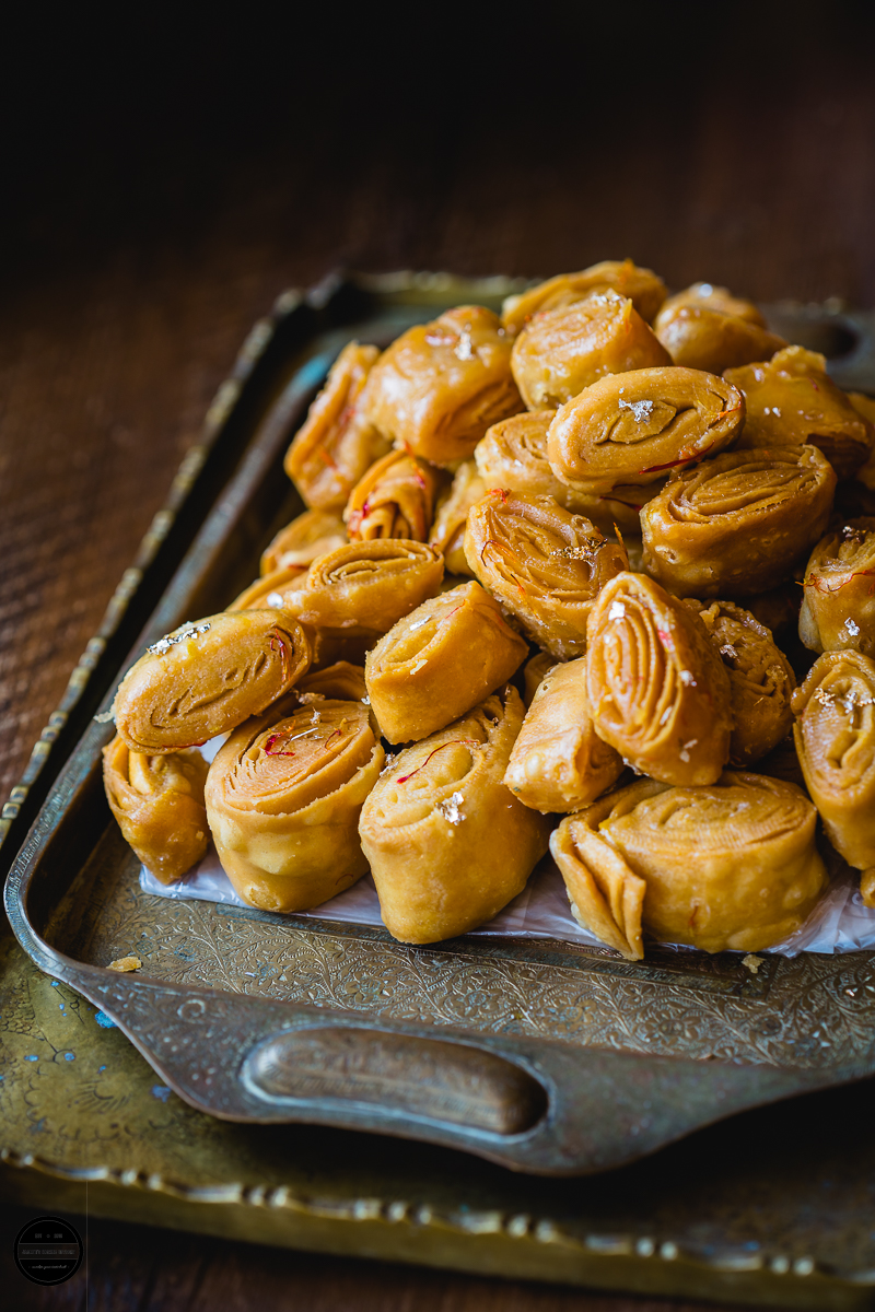 Kesar Khaja is a sweet layered pastry that is soaked in a sugar syrup.