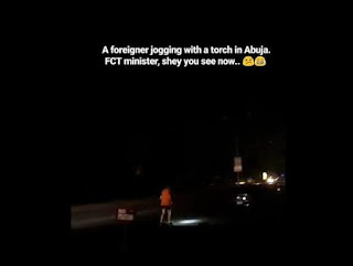 Lack of electricity forces a foreigner to jog at night with torchlight in Nigeria (Video)