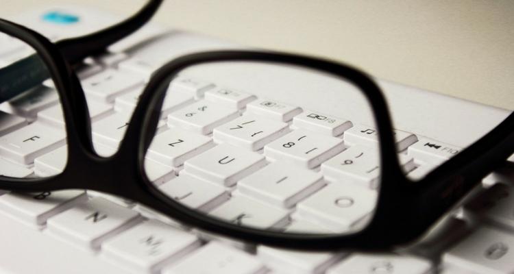 """Okulary """"kujonki"""" leżące na klawiaturze."""