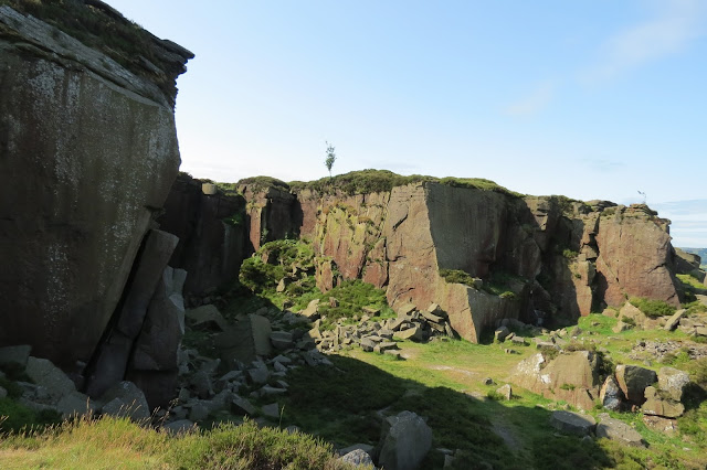 A view of the quarry, with sheer rock faces like man-made cliffs.