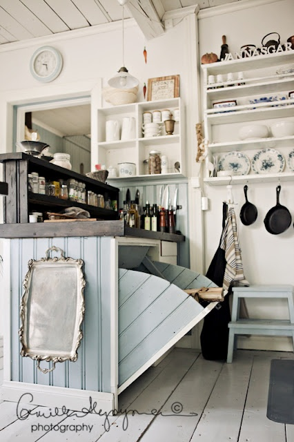 These cubby cabinets and whitewashed pallet floor are cozy elements of this farmhouse kitchen
