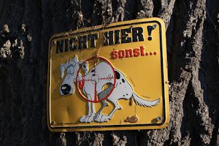 """Ein Blechschild an einem Baum. Darauf steht """"Nicht hier sonst ..."""". Ein Hund ist darauf abgebildet der im Fadenkreuz steht"""