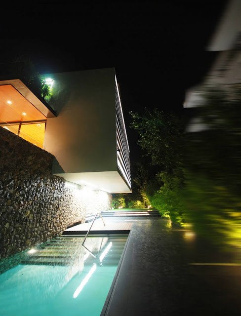 Picture of the pool by the house wall at the entrance at night