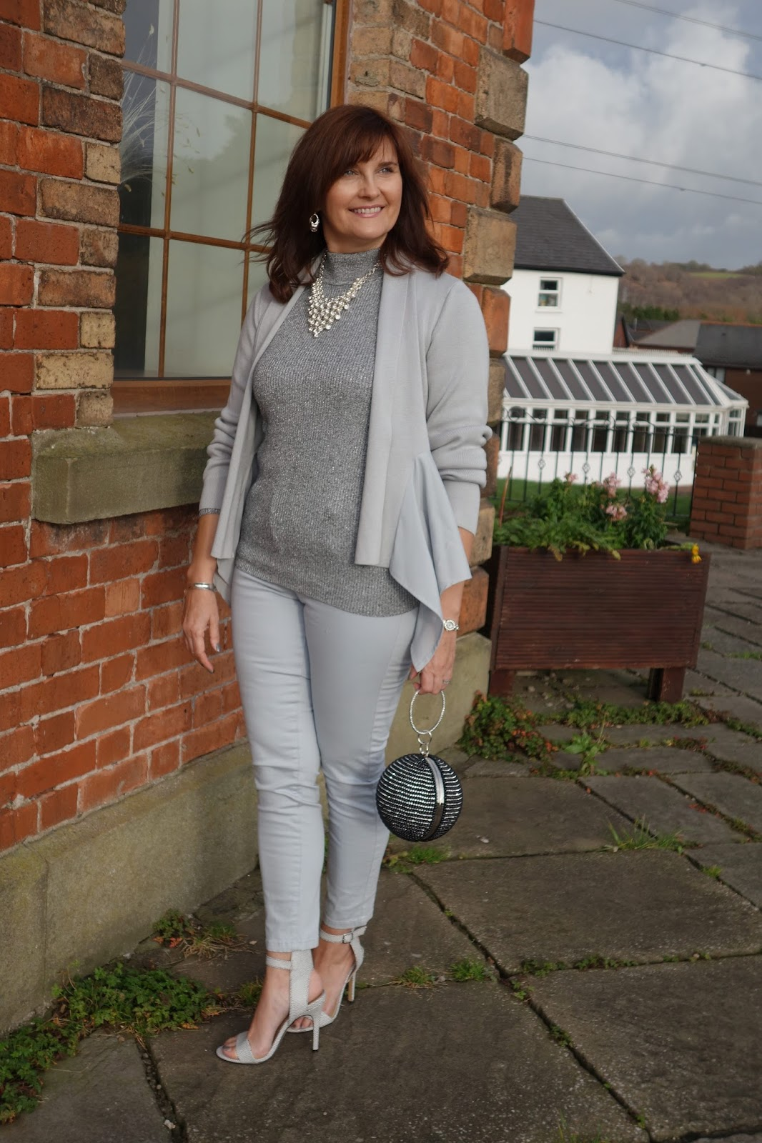 Michelle, The Barefaced Chic wears grey Christmas outfit with statement bag and heels