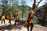 A fire crew hikes past McClure Reservoir in New Mexico en route to conducting a prescribed burn. (Credit: Alan W. Eckert) Click to Enlarge.