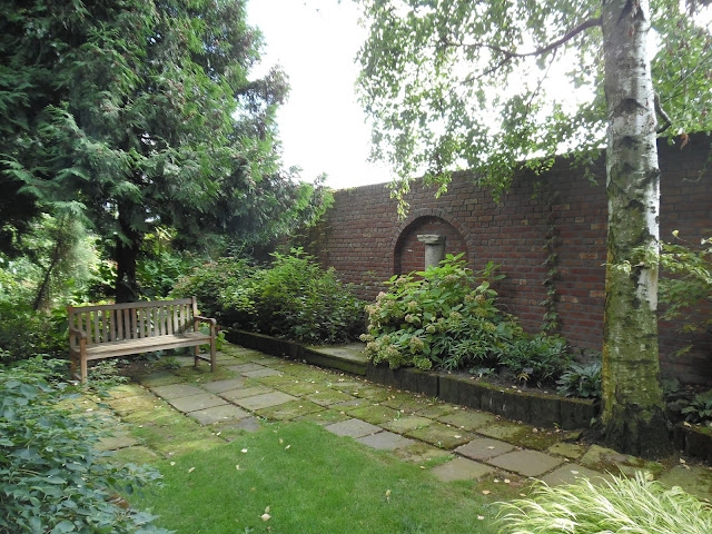 mur ceglany w ogrodzie, ogród cienisty