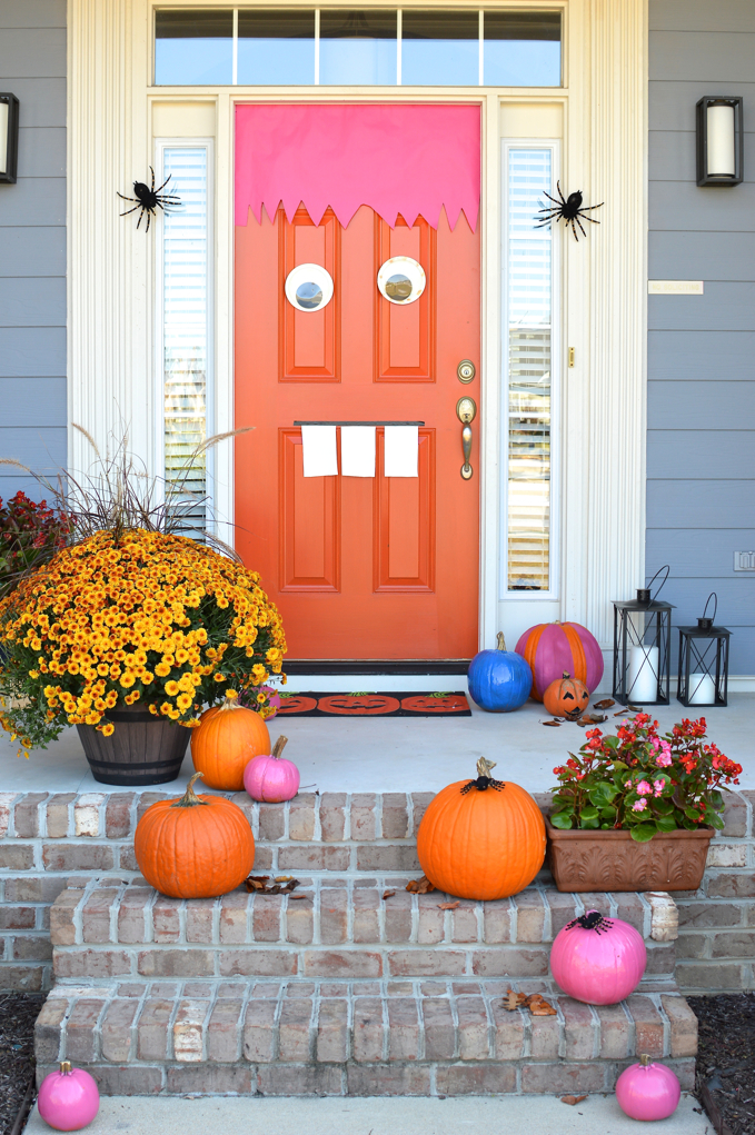 DIY Monster door, colorful pumpkins, fall flowers, and decor make this front door entrance stand out.