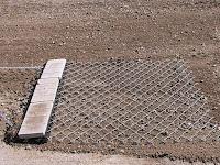 Tel örgüden yapılmış bir tapanın toprak üzerinde çekilmesi