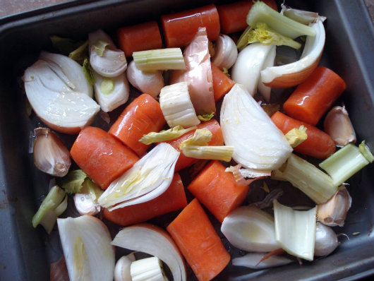Place all the vegetables and garlic into the middle of a roasting tray