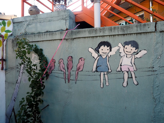 Street art of children with wings and birds on a phone line, in the Haenggung-dong mural village in Suwon, South Korea