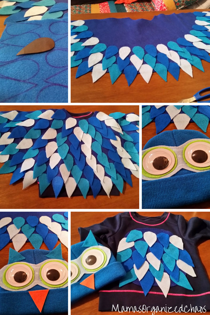 Blue ski hat turned into an owl with big google eyes and an orange nose, lying on a blue sweatshirt that has teardrops added to look like owl feathers for an O the Owl Halloween costume.