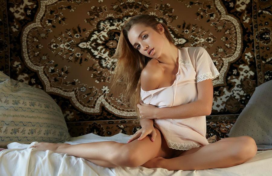Красивая девушка в деревне раздевается на фоне ковра